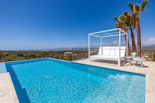 Impressive pool area with sun bed